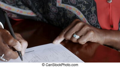 Senior black woman over 50 filling out medical history form...
