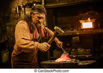 Senior blacksmith forging the molten metal on the anvil in...