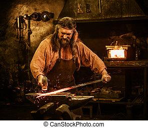 Senior blacksmith forging the molten metal on the anvil in...