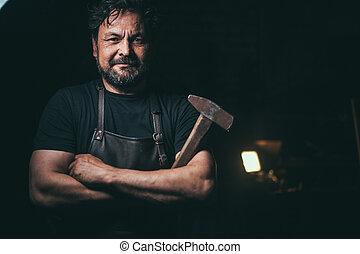 Senior blacksmith in smithy. - portrait of Senior bearded...
