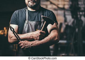 portrait of Senior bearded blacksmith in smithy workshop