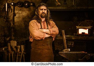 Senior blacksmith in smithy - Senior blacksmith standing in...