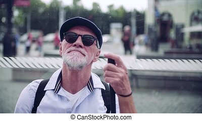 Senior blind man with white cane waiting at bus stop in city...