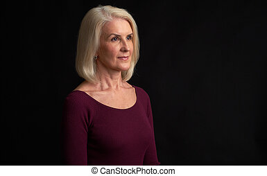 Senior blonde woman looking away isolated on black