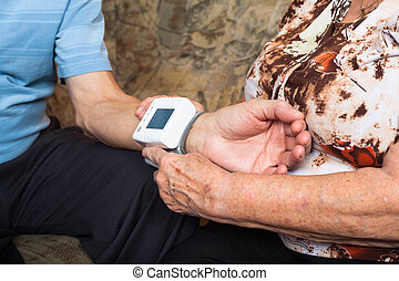 Close up of seniors checking blood pressure.