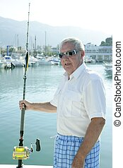 Senior boat fisherman white hair, angler fishing rod