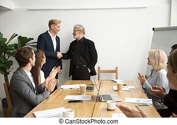 Senior boss promoting employee shaking hands team applauding at