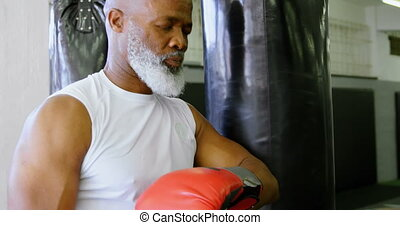Senior boxer leaning against the punching bag 4k - Tired...