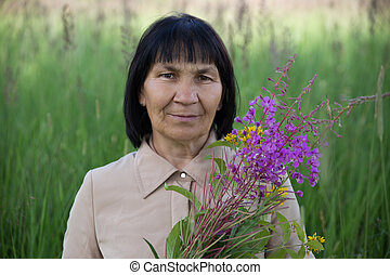 Senior brunette woman with flowers