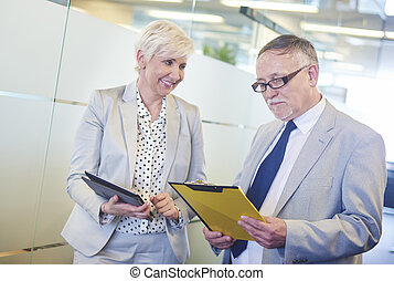 Senior business couple doing comparison of documents