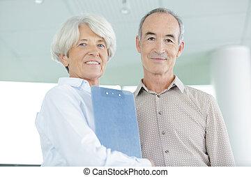 senior business couple looking at camera