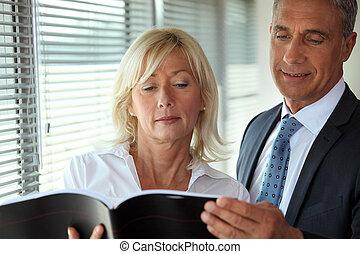 Senior business couple reading through document