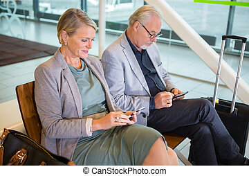 Senior business couple using mobile phones while sitting on chairs in airport lobby