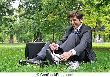 Senior business man changing shoes in park - Senior business...