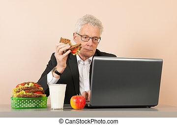 Senior business man eating bread - Senior business man with...