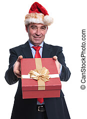 business man in santa hat offering a present box