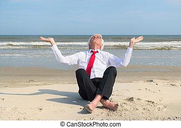 Senior business man meditation at the beach