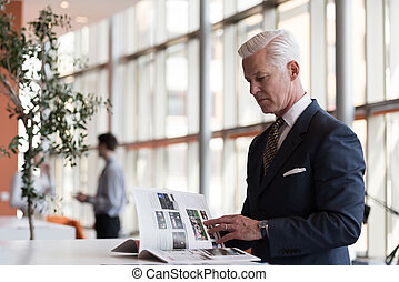 senior business man reading magazine