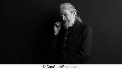 Senior business man with long hair and beard in dark business clothes standing sideways in semi-lit room on black background. Black and white portrait. Mature man on black background. Prores 422.