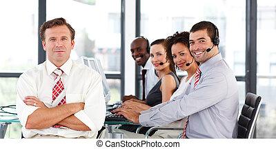Senior businessman standing in a call center