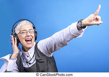Senior business woman dancing to the beat of the music
