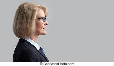 Senior business woman profile portrait. Isolated on grey