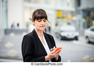 Senior business woman with phone in street