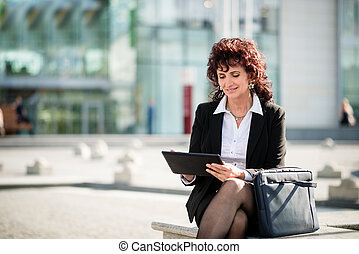 Senior business woman with tablet in street