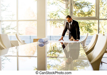 Senior businessman analyzes a project in the office on table
