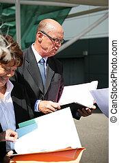 senior businessman and businesswoman reading documents