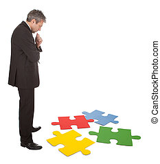 Senior businessman assembling a jigsaw puzzle. Isolated in...