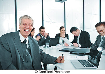 Senior businessman at a meeting. Group of colleagues in the background