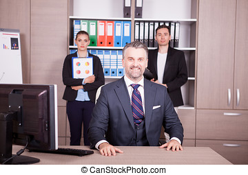Senior businessman at the desk and his colleagues in the backgro