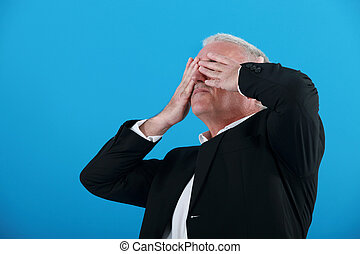 senior businessman covering his eyes with his hands