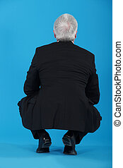 Senior businessman crouching with his back to the camera