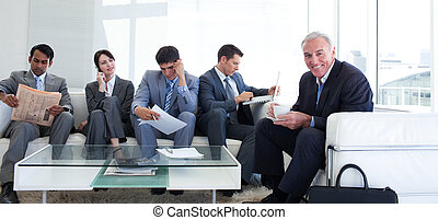 Senior businessman drinking a coffee in a waiting room