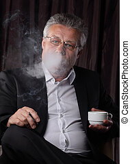 senior businessman drinking coffee and Smoking,sitting in the chair.