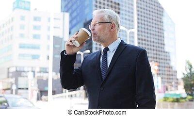 senior businessman drinking coffee on city street