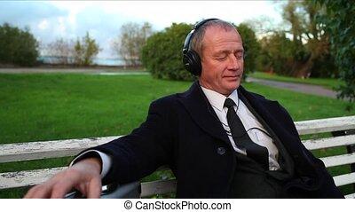 Senior Businessman Enjoying Music