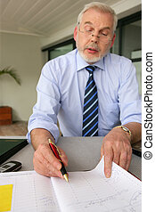 Senior businessman filling in diary