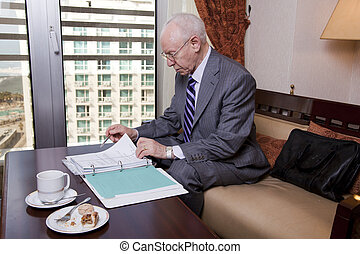 Senior Businessman Going Over Papers