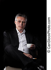 businessman holding a cigarette and a Cup of coffee