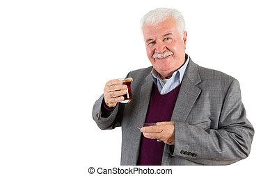Senior Businessman Holding a Glass of Turkish Tea