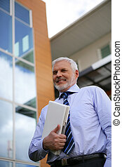 Senior businessman holding laptop outdoors
