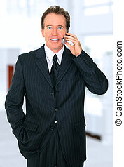 Senior Businessman In Office Lobby Talking On The Phone