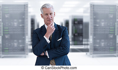 Senior businessman in server room - Portrait of senior...