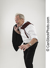 Senior businessman leaning forwards into wind in a stooped ...
