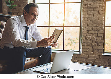 Senior businessman looking at photo with sadness