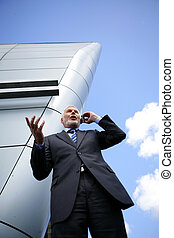 Senior businessman making a call outside a modern building