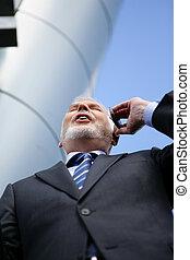 Senior businessman making a call outdoors